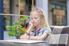 Милое меню чтения ребенка в кафе Стоковое Изображение RF