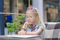 Милое меню чтения ребенка в кафе Стоковое фото RF