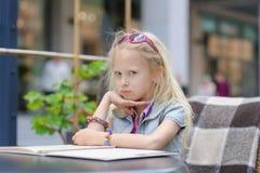 Милое меню чтения ребенка в кафе Стоковые Фото
