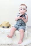 Милое модно одетое 10 месяцев ребёнка сидя на чемодане Стоковые Фотографии RF