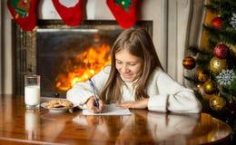 Милое письмо сочинительства девушки к Санта Клаусу на Рожденственской ночи Стоковые Изображения