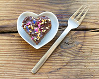 Милое сердце сформировало часть шоколадного торта взбрызнутую с цветками Стоковая Фотография