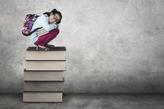 Милое сидение на корточках студента на книгах Стоковое Изображение RF