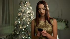 Милое усмехаясь платье золота дамы нося, представляя на камере с smartphone на ее руках приближает к рождественской елке видеоматериал