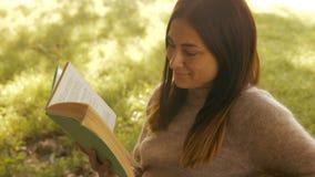 Милое чтение брюнет в парке акции видеоматериалы