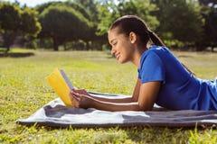 Милое чтение женщины в парке стоковое изображение rf
