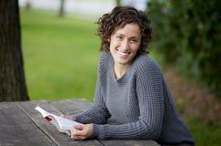 Милое чтение женщины на парке Стоковые Изображения