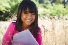 Милое чтение маленькой девочки в парке Стоковое фото RF