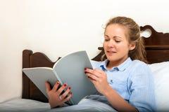 Милое чтение молодой женщины на кровати Стоковые Изображения RF