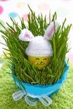 Милое яичко в шляпе зайчика на зеленой траве Стоковое Изображение