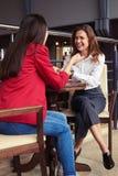Милые бизнес-леди говоря шутки и ослабляя с чашкой esp Стоковые Изображения