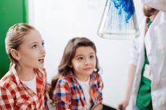 Милые выведенные девушки смотря химическую реакцию Стоковое Фото