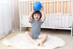 Милые 2 года мальчика играют с шариком фитнеса внутри помещения Стоковое Изображение RF