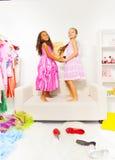 Милые девушки держат руки и скачку на белой софе Стоковые Фото