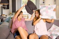 Милые девушки делая бой подушками дома смеясь над счастливой широкой съемкой Стоковая Фотография