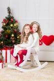 Милые девушки играя в рождестве украсили комнату Стоковое фото RF