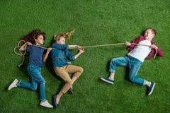 Милые девушки и мальчик лежа на траве и играя перетягивание каната Стоковые Фото