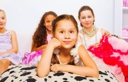 Милые девушки кладя и сидя на удобной кровати Стоковые Изображения RF