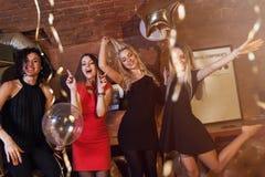 Милые девушки нося платья коктеиля имея вечеринку по случаю дня рождения околпачивая вокруг танцевать в ночном клубе стоковое изображение rf