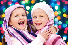 Милые девушки обнимая и смеясь над совместно на Рожденственской ночи Стоковые Фотографии RF