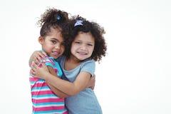 Милые девушки обнимая и смотря камеру Стоковое Изображение