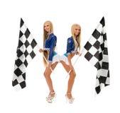 Милые девушки представляя с checkered флагами на камере Стоковые Изображения
