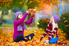 Милые девушки, друзья имея потеху в красочном парке осени, меча листья вверх Стоковое Фото