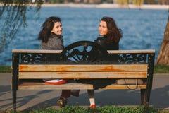 Милые девушки сидя на деревянной скамье, усмехаясь Стоковая Фотография