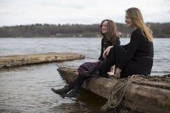 Милые девушки сидя на журнале и смеясь над около реки Природа Стоковые Изображения RF