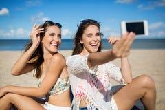 Милые девушки сидя на пляже принимая смеяться над selfie Стоковые Фотографии RF