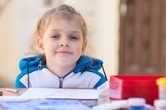 Милые девушки сидя на таблице в дворе, посмотренном вверх от чертежа и посмотренном в рамку Стоковая Фотография RF