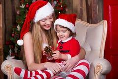 Милые девушки сидя с настоящими моментами приближают к рождественской елке в костюмах Санты, усмехающся и имеющ потеху Атмосфера  Стоковое фото RF