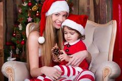 Милые девушки сидя с настоящими моментами приближают к рождественской елке в костюмах Санты, усмехающся и имеющ потеху Атмосфера  Стоковое Изображение