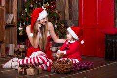 Милые девушки сидя с настоящими моментами приближают к рождественской елке в костюмах Санты, усмехающся и имеющ потеху Атмосфера  Стоковые Фото