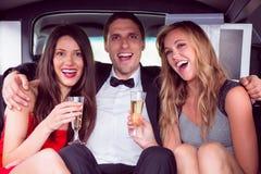 Милые девушки с человеком дам в лимузине Стоковые Изображения