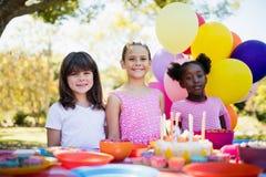 Милые девушки усмехаясь и представляя во время вечеринки по случаю дня рождения Стоковое фото RF