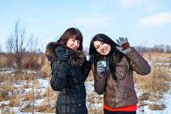 Милые девушки усмехаясь с чашками чаю Стоковое Фото