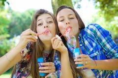 Милые девушки дуя пузыри мыла счастливый в парке Стоковая Фотография RF