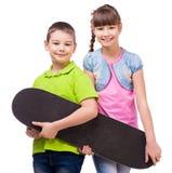 Милые дети держа скейтборд в руках Стоковые Фото