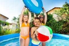 Милые дети играя в большом раздувном бассейне снаружи Стоковая Фотография