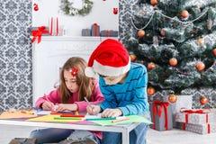 Милые дети писать письмо к santa, ожидание для рождества Стоковые Фото