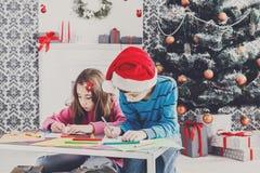 Милые дети писать письмо к santa, ожидание для рождества Стоковые Изображения RF