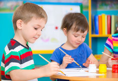 Милые дети рисуя с красочными красками на детском саде стоковые изображения