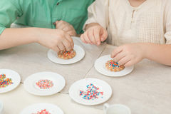 Милые дети украшают печенья на таблице в домашней кухне Стоковая Фотография RF