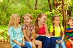 Милые дети читая сказки сидя в парке Стоковые Изображения