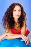Милые женщины волос скручиваемостей на голубом шарике pilates стоковое фото rf
