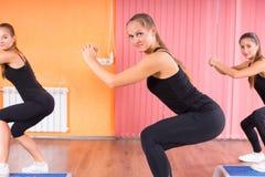 Милые женщины в тренировке сидеть на корточках внутри спортзала Стоковое Фото