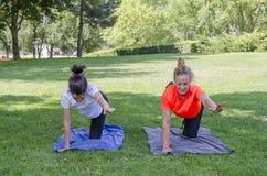 Милые женщины делая йогу работают в парке Стоковое Фото