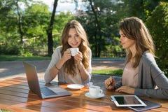 Милые женщины сидя outdoors в кофе парка выпивая используя компьтер-книжку стоковые фото