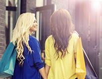 Милые женщины с хозяйственными сумками outdoors Стоковая Фотография
